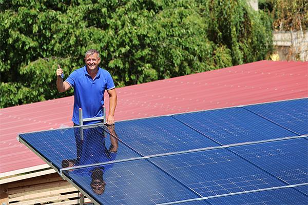 Mann steht vor Solarpanelen und zeigt Daumen nach oben