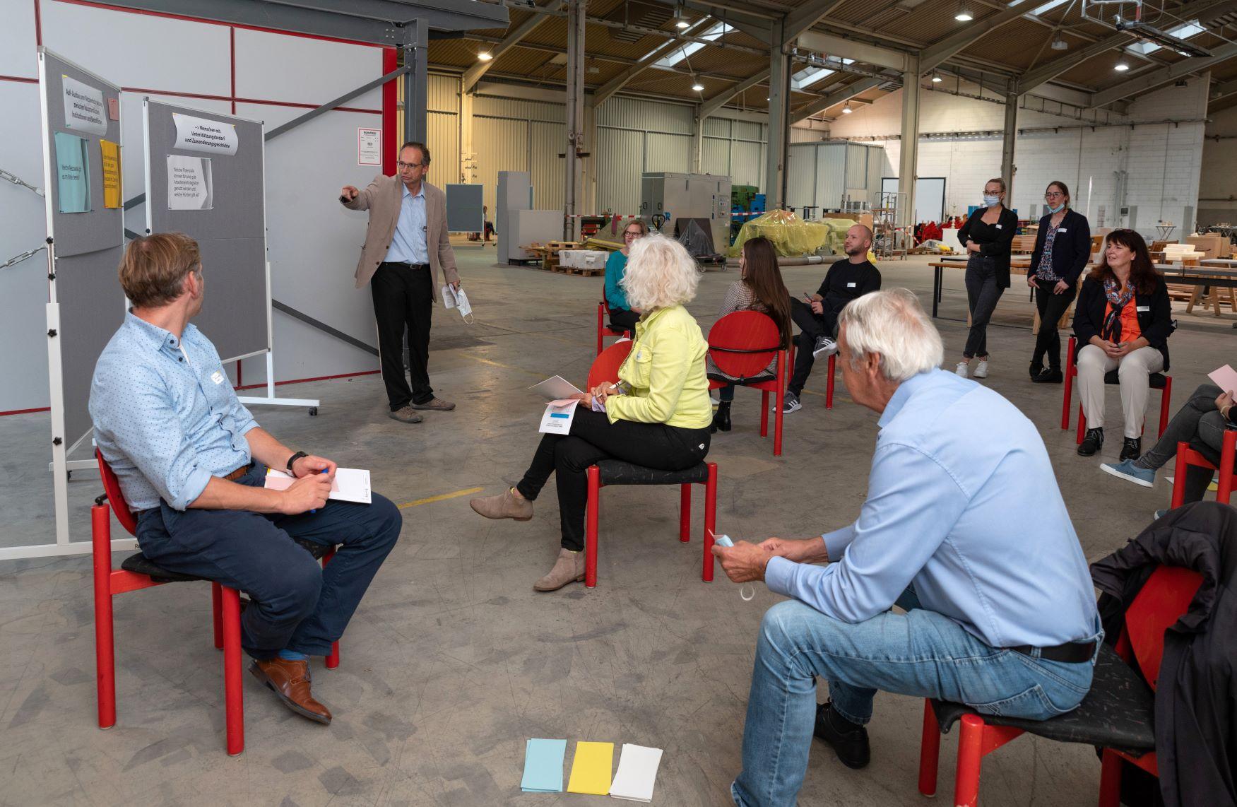 Foto 3 zeigt Dr. Rolf Hackenbroch (Stabsstelle Integration)  in Diskussion mit den Teilnehmenden